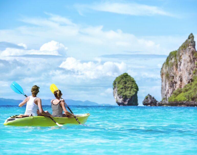 Two ladies are kayaking or kanoeing at beautuful tropical lagoon at Phi-Phi islands. Krabi province, Thailand